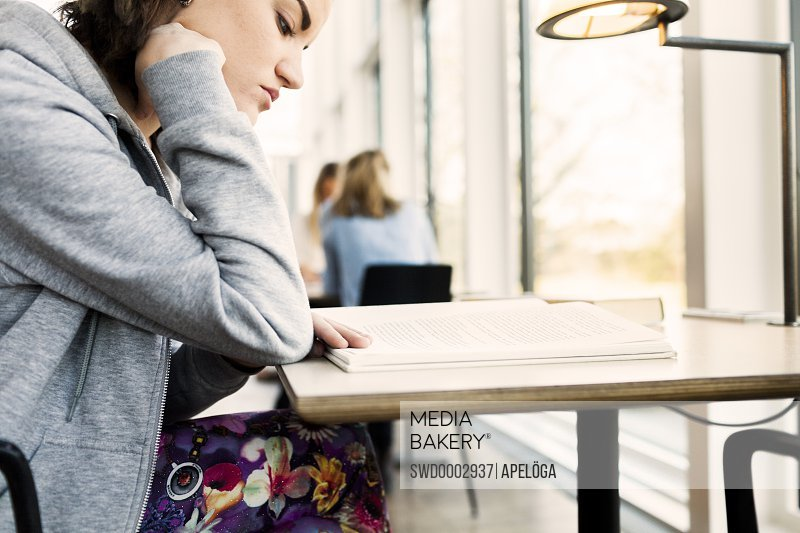 Side view of young woman reading book at table in library