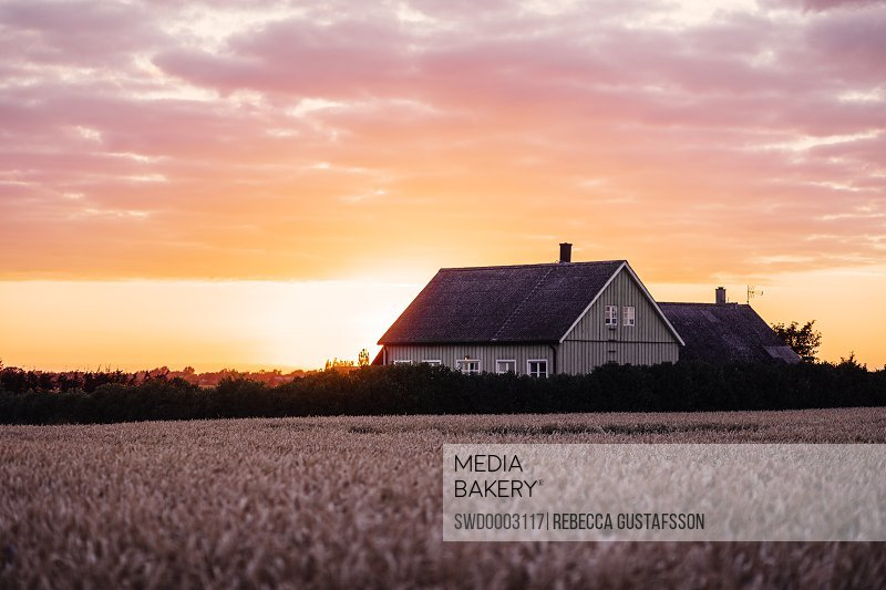 Exterior of house on field against cloudy sky during sunset