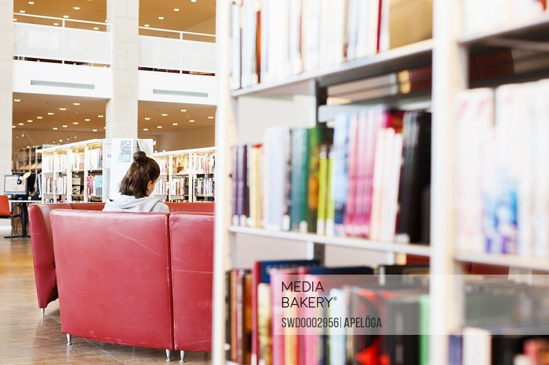 Rear view of woman sitting on sofa in library