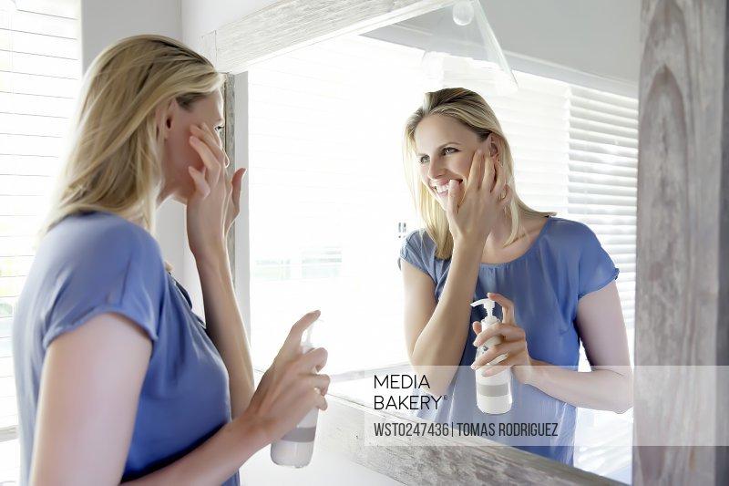 Woman in bathroom applying skin cream